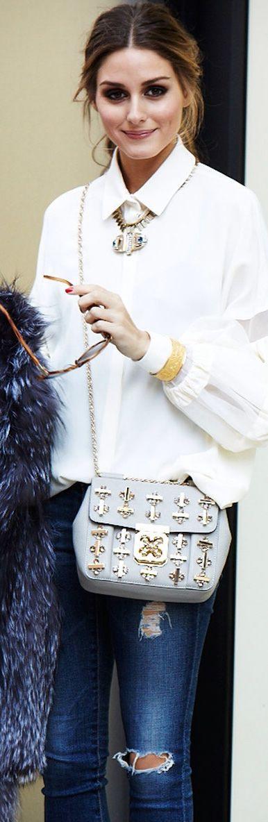Olivia Palermo arrasando no look HiLo, com camisa clássica e jeans rasgado e detalhe especial para a bolsa cheia de aplicações em dourado, combinando com o colar de pedras. Além disso, um acessório usado de forma original é o bracelete por cima da manga.