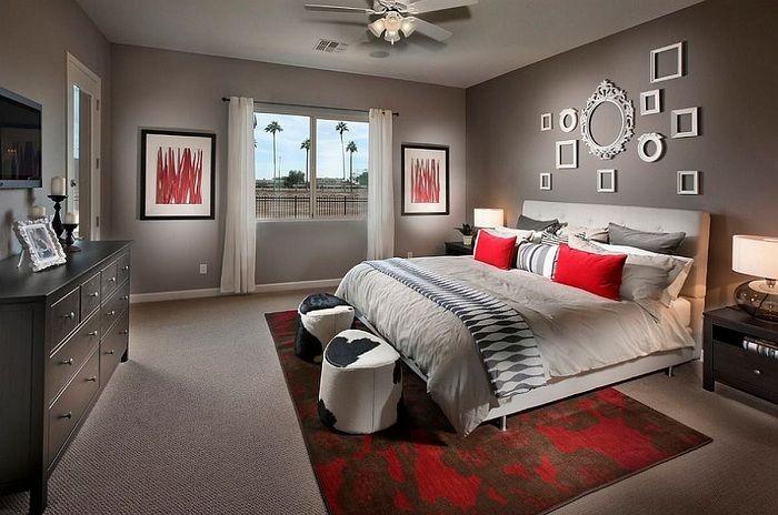 Спальня в серых тонах инкрустирована с помощью красных элементов в интерьере и белых рамок на стене, которые отлично вписываются в интерьер.