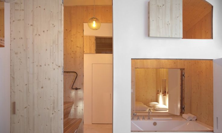 The compact ground level of each tiny wooden house features a snug bedroom, sauna, toilet and kitchen.