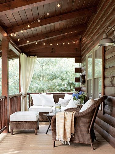String lights from @Target twinkle over the front porch, and  @Vicki Smallwood Snyder Barn wicker furniture surrounds an antique folding table.