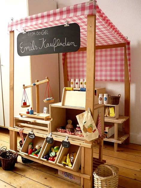 A DIY play grocery store, said to be made of salvaged wood and other recycled materials at home: left over fabric, table cloth, shower curtain, bins, wooden shoe racks, baskets, etc.