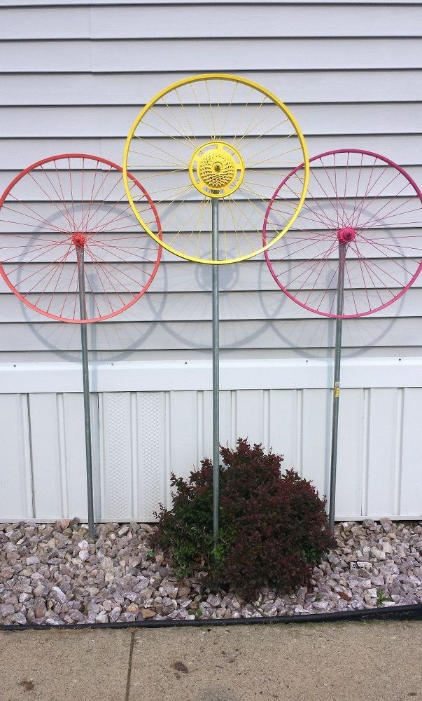 Bicycle Wheel Yard Art: Gather some old bike rims, then loosen the bolts on the axle. The image above on the left is how a bike rim axle normally looks and the image on the right the axle has been threaded through so it extends out on one side. Both sides require their bolts be put back on. Wipe the bike rim down completely with mineral spirits so your paint will stick. Buy a few rods of electrical metal conduit at your local hardware store. One for each wheel. See tutorial at source.