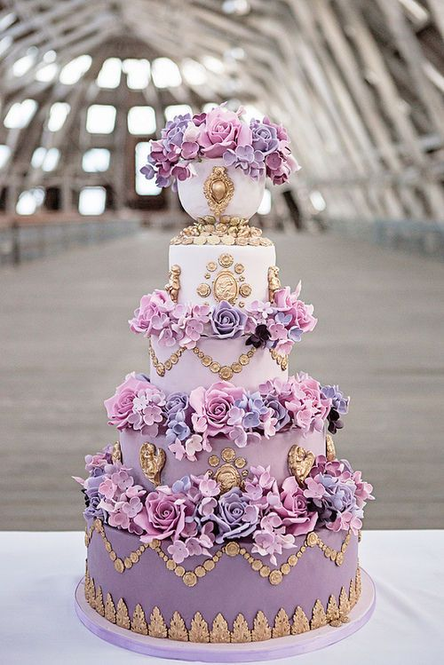 One very beautiful purple & gold wedding cake.