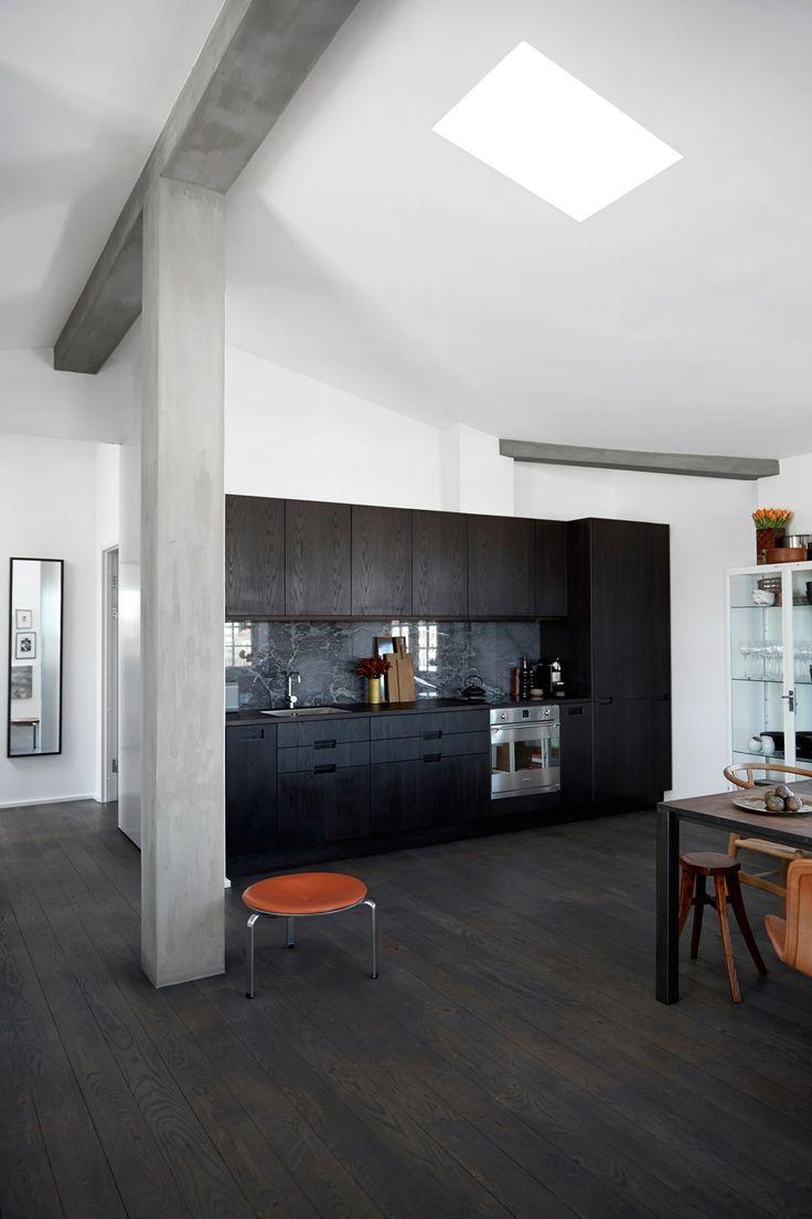 Køkkenet i røget eg fra Cph Square, som har smukke detaljer, fx et smalt højskab til vin og en grå vægplade i marmor. Skærebrætter fra Raumgestalt.Taburetten er af Poul Kjærholm, og den under spisebordet er kinesisk og fra Green Square. For at understrege, at det store rum har forskellige funktioner, har han malet en søjle og loftsbjælker i en kitfarve, så øjet opdeler lokalet.  / Uffe Buchard