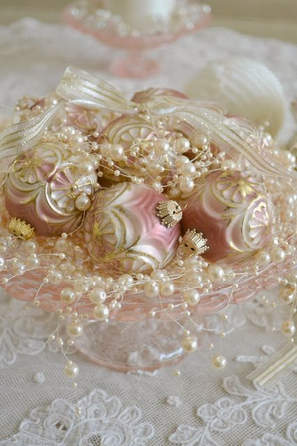 Ornate pink and white holiday ornaments with gold trim!!! Bebe'!!! Displayed in a pink depression glass bowl surrounded by pearls and with a Lacey white ribbon and bow on top!!!