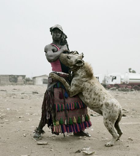 """i do not """"promote"""" humans owning wild animals by pinning this.  it is a very interesting article about the hyena men of africa at the link.  it is about their traditions and practices as a family.  they use large sticks to beat the hyenas (very bad) and they gave their littlest family members special herbs and concoctions so they will never be hurt by the animals.  the herbs allow the little ones to play freely with the animals and ride them. (scary stuff!) click link for story."""