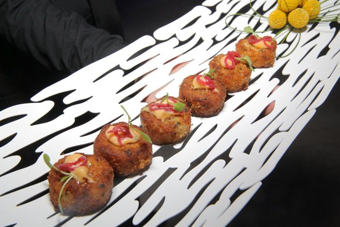 At a Los Angeles event hosted by Century 21 Real Estate in July with a futuristic look and feel, hors d'oeuvres—such as lump crab cakes with remoulade and micro arugula—were served on modern-style white platters that included unusual cutout forms.