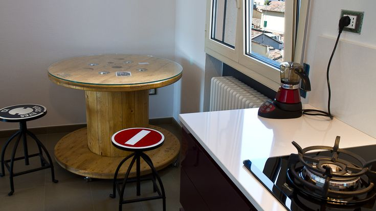 Wooden reel table with Round Glass top with random family photos placed under Glass. Would serve as extra table and seating in Bar Area