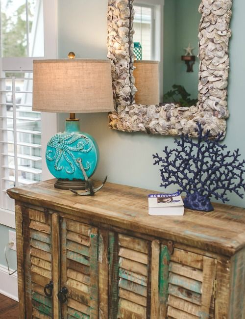 Oyster shell mirror... http://www.completely-coastal.com/2016/05/the-colorful-coastal-cottages-at-ocean-isle.html