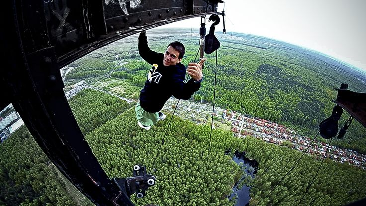 Russian daredevil dangles perilously from cranes and buildings