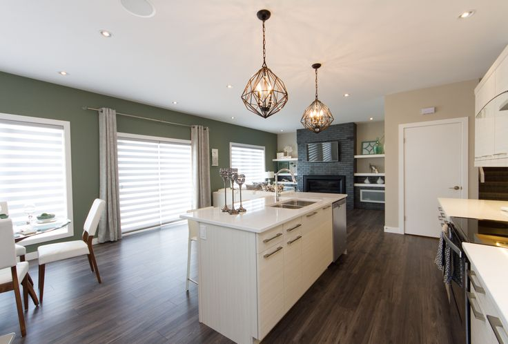 Open concept galley kitchen, dining room and living room with island.