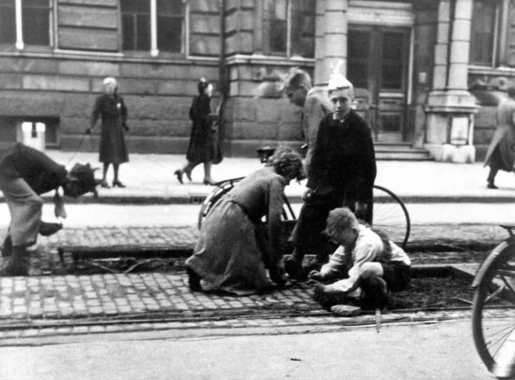 Hunger winter in Amsterdam, 1944. With no food and no coal to burn in their stoves people removed wood blocks from the tram tracks.