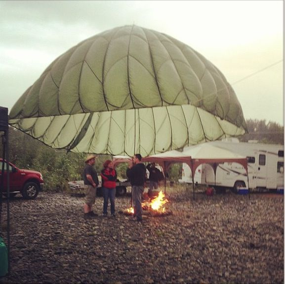 We used a Parachute for our camp fire!  Perfect rain shelter.