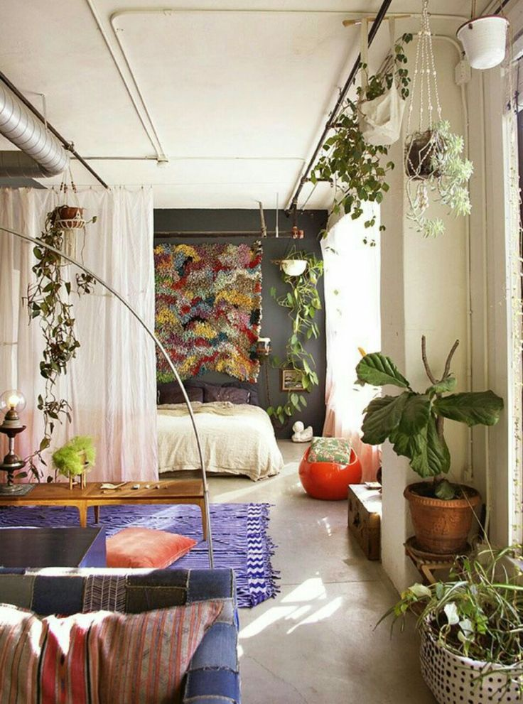 There is nothing cold or industrial about this loft's interior.  Tapestries, worldly textiles, and plants, act to cozy up an urban living space.
