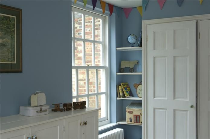 A children's bedroom with walls in Lulworth Blue Estate Emulsion and woodwork in Wimborne White Estate Eggshell.