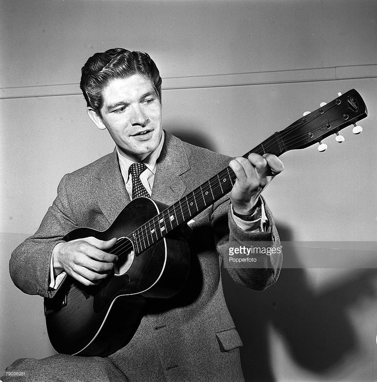 Cinema, England, 1955, Irish born film actor Stephen Boyd is pictured playing a guitar