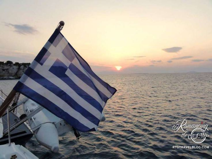 Greek flag on our sailboat at sunset