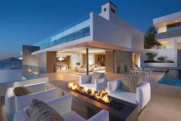 Aus glass und luxus feuerstelle im weißen haus mit blick aufs meer