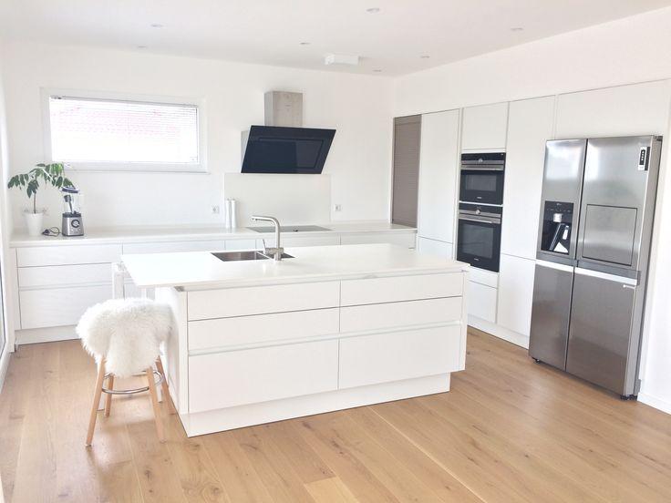 Küche ganz in weiß mit Keramikarbeitsplatte, Spülinsel und großen Side by side Kühlschrank