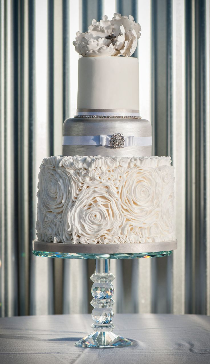 Ivory and silver wedding cake with ruffled detail