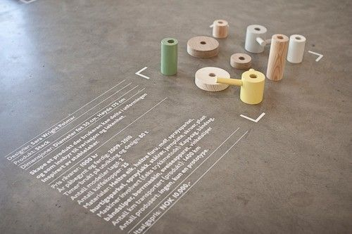 pastel colours mixed with wooden cylinders and white text vinyl applied to polished concrete floor