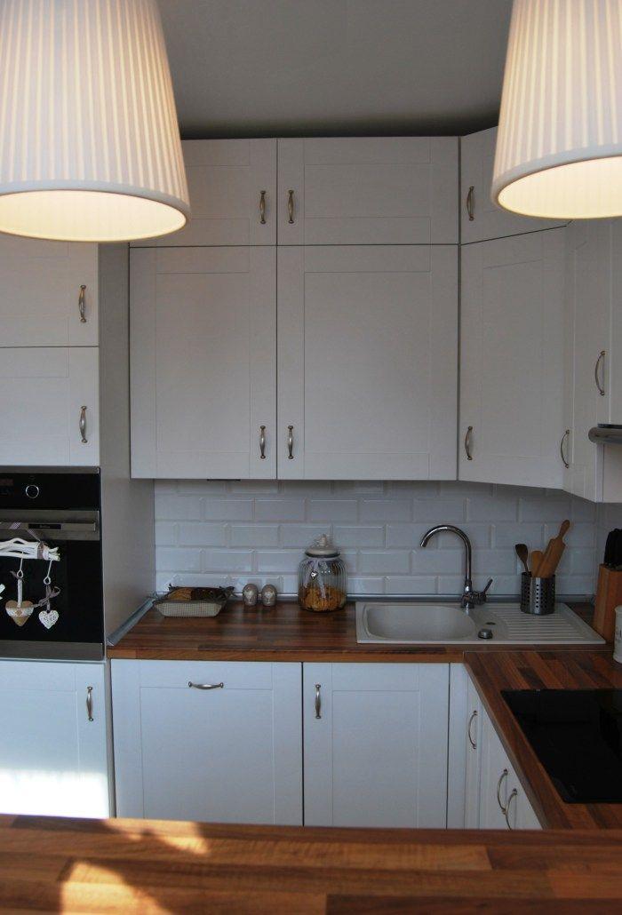 Biała kuchnia z drewnianym blatem.  White kitchen with wooden worktop