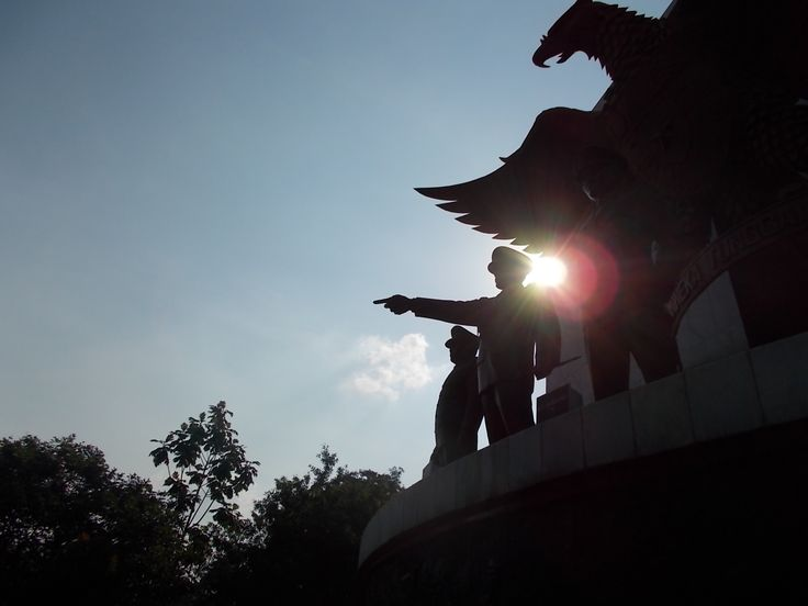 Silhouette of Ahmad Yani Statue with its pointing arm, and other statues in Pancasila Sakti Monument, Jakarta.