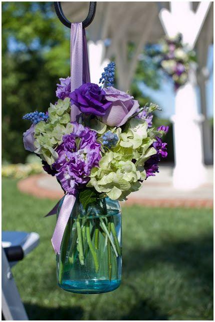 Blue mason jar, green hydrangea, purple stock, purple rose, green hypericum berries, grape hyacinth Loda Floral Design