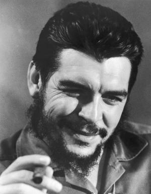 Who Was Che Guevara?: Closeup of Ernesto 'Che' Guevara, Cuban minister of finance, smoking a cigar in military fatigues. (circa 1959)