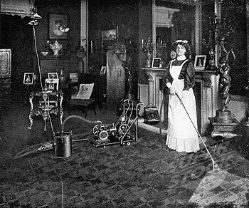 Maid vacuuming carpet, 1911 (using a natural gas powered vacuum cleaner, attached to the gas chandelier ...yikes!)