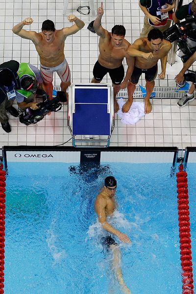 Michael Phelps looks on from the water after earning his record 19th Olympic medal while his teammates celebrate their win in the 4x200-meter freestyle relay.