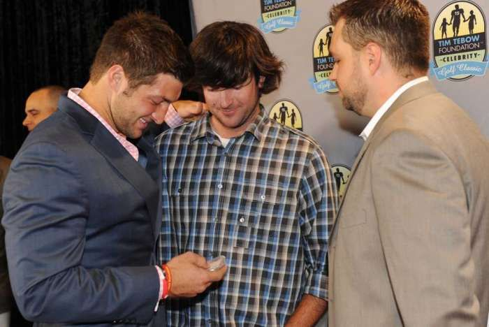 Masters champion Bubba Watson (center) presents Tim Tebow (left) with Watson's Masters badge at an event for the Tim Tebow Foundation Celebrity Golf Classic on Friday night. The badge is No. 15, which is Tebow's Number.