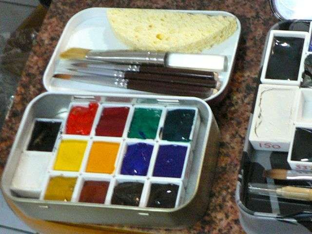 Travel watercolor kit using Altoids tin, small pans filled with watercolor paints dried, a sponge and cut off paint brushes.