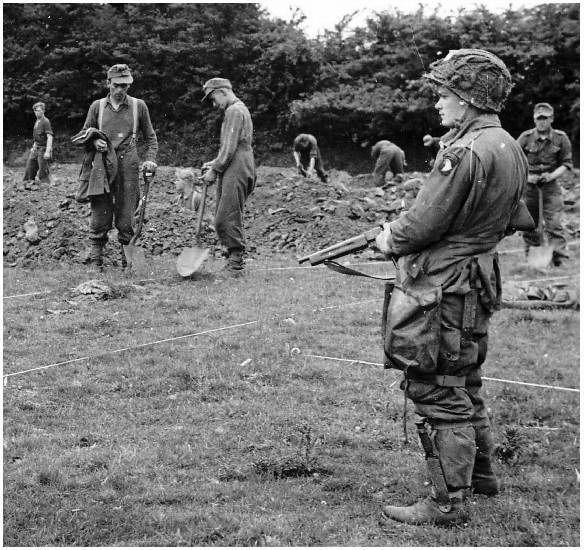 101st airborne easy company   Een para van de 101st ziet er op toe dat Duitse gevangen graven delven
