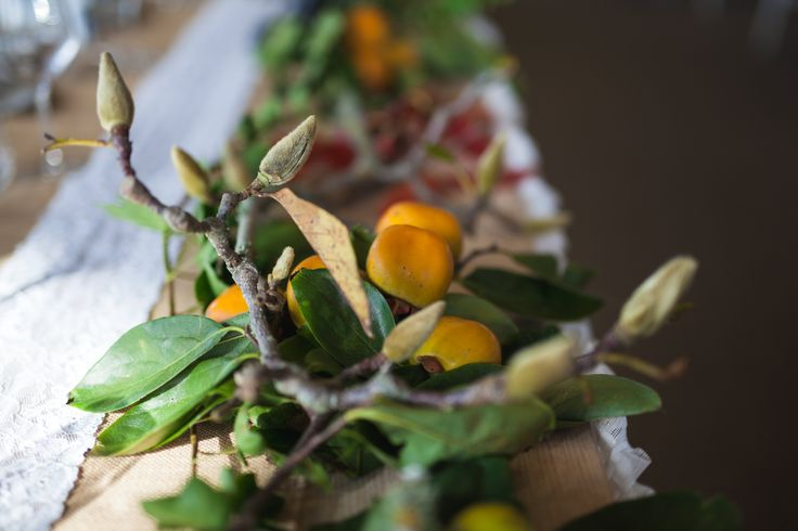 lush persimmon branches with magnolia buds table runners. by febella flowers