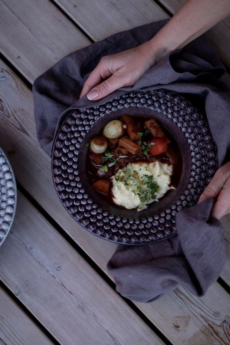 4. Skala pärllöken och behåll dem hela, lägg dem i grytan och låt koka i 10 minuter utan lock så att såsen reduceras, den ska täcka baksidan av en sked. 5. Stek champinjonerna hela i lite olja tills de är gyllene. Lägg dem i grytan och rör runt så att allt blir varmt. 6. Servera med potatismos och hackad persilja.
