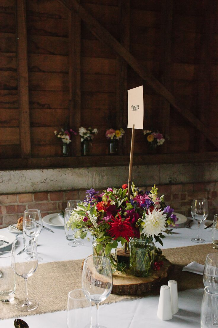 Rustic Tree Slice & Flowers in Jars Centrepiece - Joanna Brown Photography | Rustic Wedding at The Great Barn Rolvenden in Kent | Bespoke Bridal Separates | Mis-Match Bridesmaid Gowns | Teal Paul Smith Suit