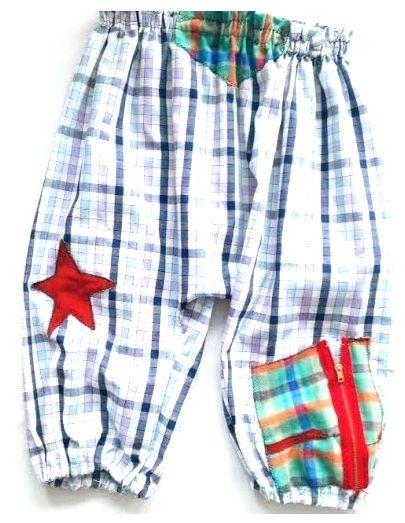 Pantalón  hippie bombacho para niño de algodón a cuadros en color blanco y azúl con parches cosidos en colores y a cuadros,  con cintura elasticada y bolsillo con cremallera mas otro bolsillo en la parte de atrás.