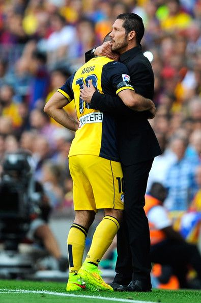 Head coach Diego Pablo Simeone of Atletico de Madrid hugs his player Arda Turan as he leaves the pitch injured during the La Liga match between FC Barcelona and Club Atletico de Madrid at Camp Nou on May 17, 2014 in Barcelona, Catalonia.