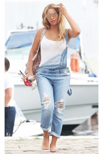 Beyonce wears denim overalls and a white tank while strolling down the beach. | essence.com