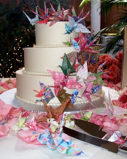 Unique three tier white Japanese style wedding cake decorated with colourful cascading japanese paper origami cranes