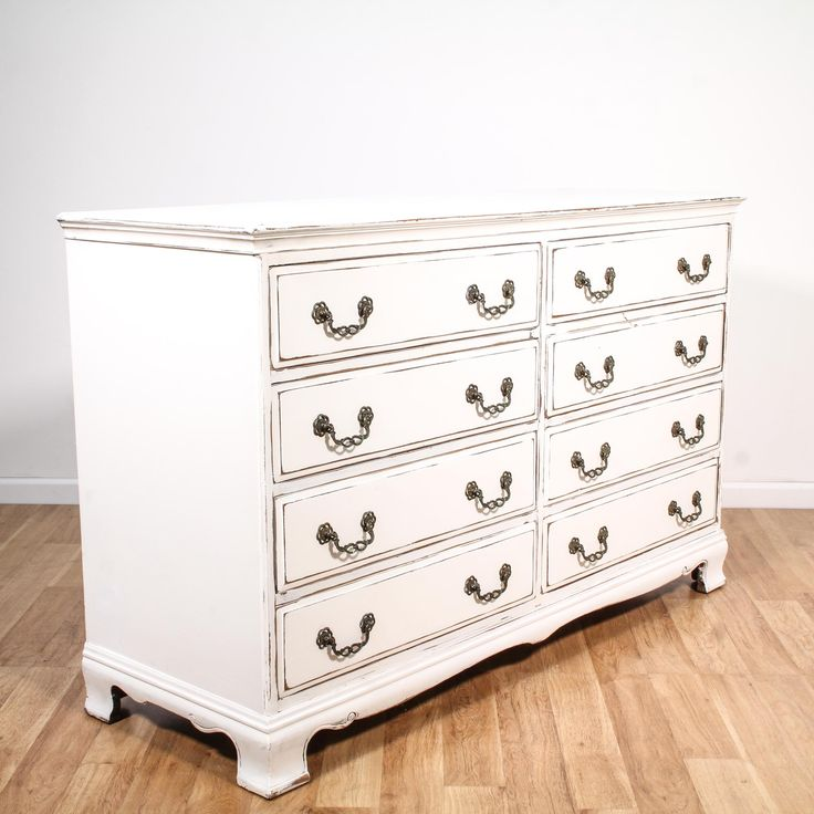 This shabby chic dresser is featured in a solid wood with a distressed white chalk paint finish. This long dresser is in great condition with 8 large drawers, curved base trim and carved metal hardware. Cottage chic storage piece perfect for organizing clothing! #shabbychic #dressers #longdresser #sandiegovintage #vintagefurniture