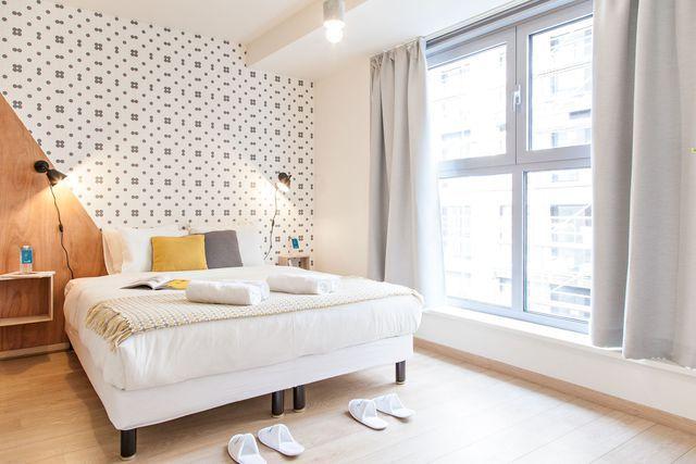 En guise de tête de lit dans la chambre du séjour, le bois et le papier peint à motifs