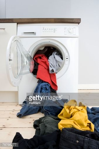 Stock Photo : Laundry spilling out of a washer dryer