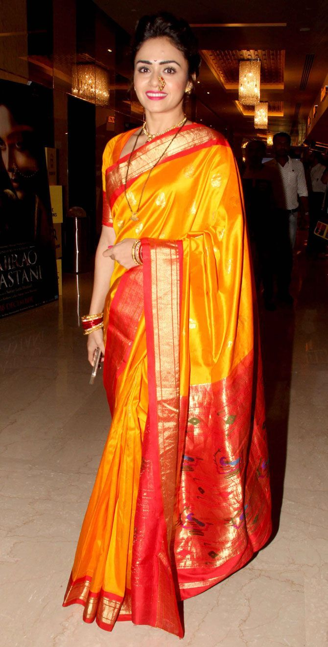 A true picture of opulence. A Paithani silk saree has a presence.  The lustre and glow of the yellow silk saree with a red border has cast a gentle glow changing the simple into extra ordinary.