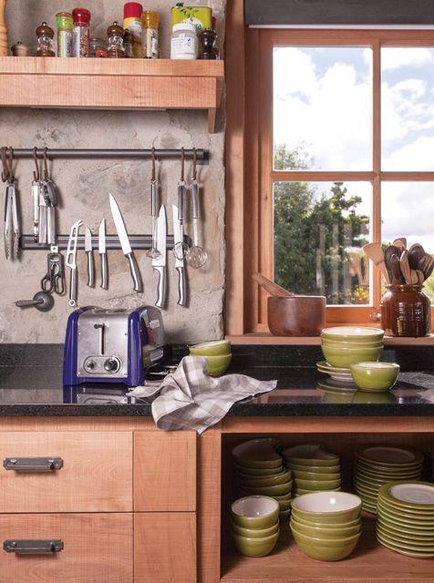 Cocina de una estancia patagónica con alacenas de madera, encimera con mármol negro, vajilla en color mostaza y barra de metal en la pared para colgar utensilios.