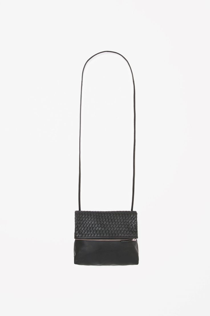 This fold-over bag is made from soft buttery leather with a braided texture. A versatile style, it has a single cotton lined compartment, an adjustable leather strap and closes with a metal zip.