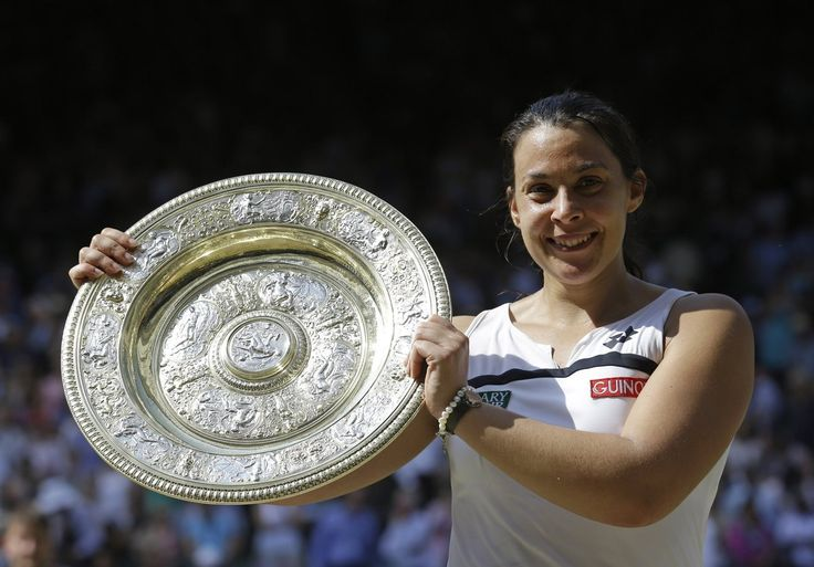 PHOTOS: Wimbledon Women's Final. Marion Bartoli of France smiles as she holds the trophy after winning the Women's singles final match against Sabine Lisicki of Germany at the All England Lawn Tennis Championships in Wimbledon, London, Saturday, July 6, 2013. (AP Photo/Anja Niedringhaus)