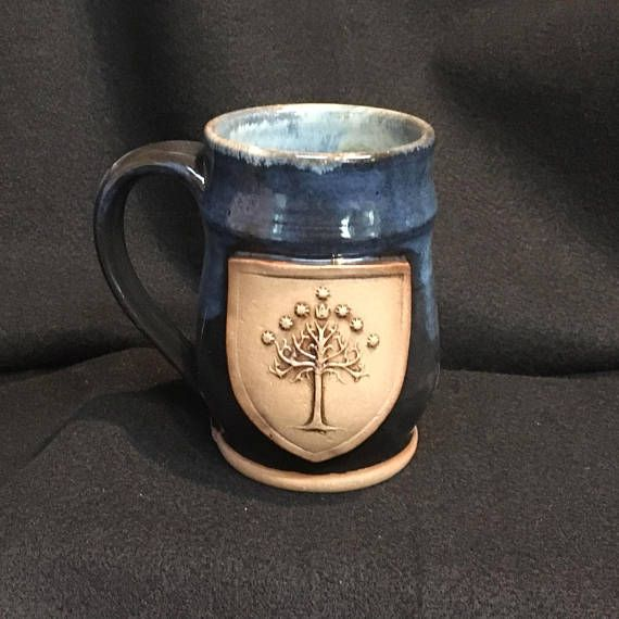 This mug features a medallion inspired by the Tree of Gondor. The medallion is washed with manganese to bring put the details. Holds approx. 16 ounces.   Glaze is indigo over midnight blue. The interior is glazed rustic mustard. Dishwasher and microwave safe.