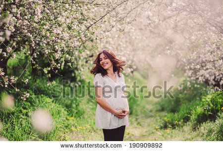 Beautiful pregnant woman relaxing outside in the park - stock photo